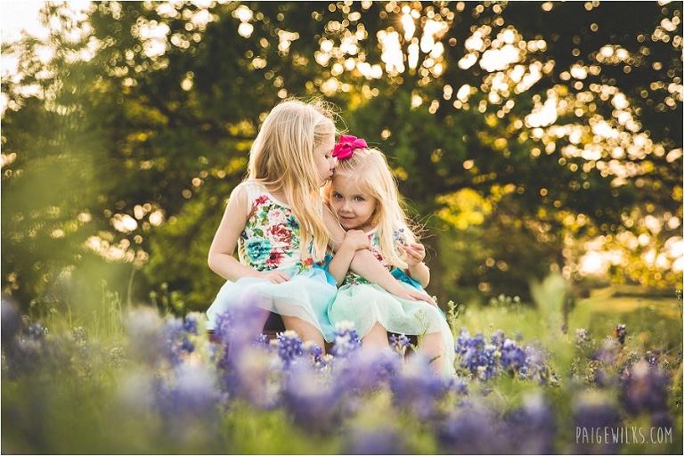 sisters kissing bluebonnets