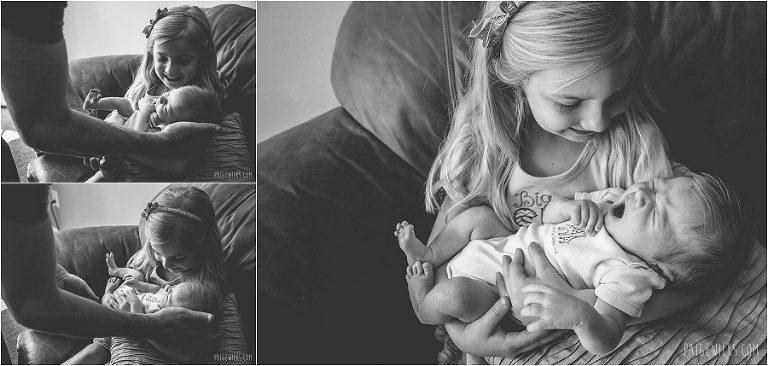 big sister holds newborn brother black and white lifestyle image